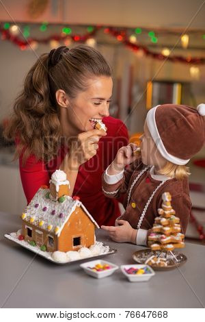 Happy Mother And Baby Eating Cookie In Christmas Decorated Kitch