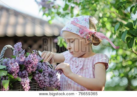 Cute little girl cutting lilacs in spring garden