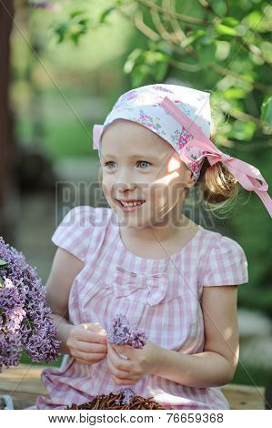 Beautiful happy little girl portrait with lilacs in spring garden