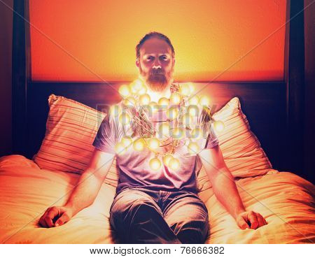 a man draped in christmas lights sitting on a bed looking depressed toned with a vintage filter
