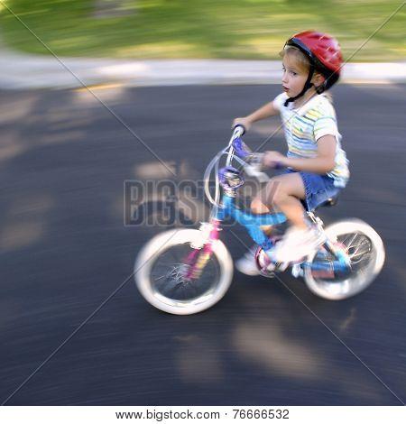 Little girl riding a bike wearing a helmet going speedy fast