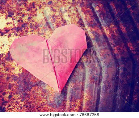a discarded paper heart on a rusty background with leaves toned with a retro vintage instagram filter effect