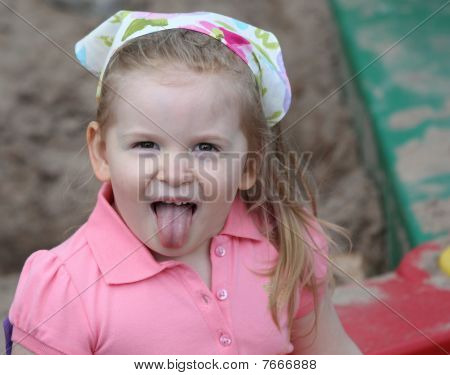 A Little Girl In Sandbox Sticking Tongue Out.