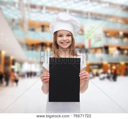 cooking, childhood, advertisement and people concept - smiling little chef girl, cook or baker with blank black paper over shopping center background