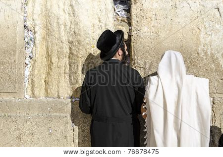 JERUSALEM, ISRAEL - FEBRUARY 19, 2012: Worshipers pray at the western wall. The wall is the most sacred site in Judaism outside of the Temple Mount itself.