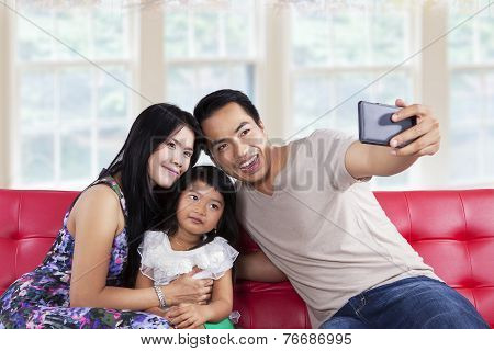 Family Posing On Camera Phone