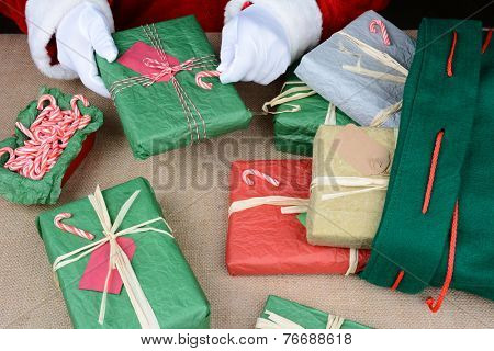 Closeup of Santa Claus as he puts the finishing touches on presents before stuffing them into his bag. Horizontal format showing only the jolly old elfs hands as he places candy canes on a gift.