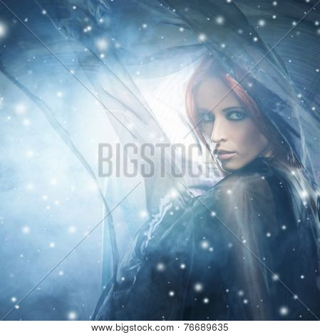 Young attractive woman in a blowing silk. Snowy background with wind, lighting and blizzard.