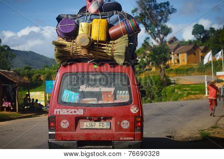 MADAGASCAR- DECEMBER 23, 2013. Overloaded bus moves on the asphalt road through the african village