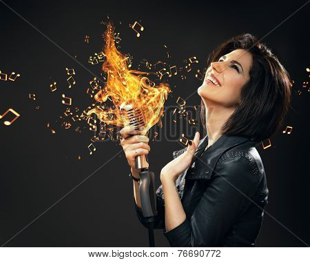 Half-length portrait of female rock musician keeping burning mic on grey background