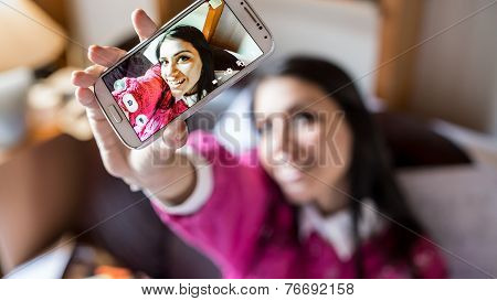 Happy pretty girl woman taking a selfie using her smartphone, taking a self portrait with her smart