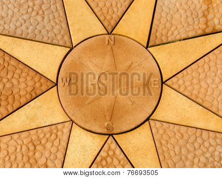 Stone Compass Rose Set Within A Star. Golden Coloured Paving Slabs.