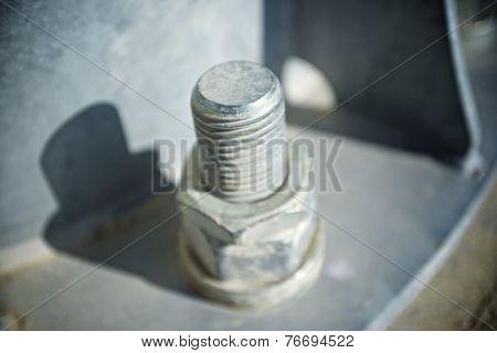 Close up of a larger screw into the base of a metal pillar.