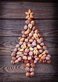 foto of hazelnut tree  - Christmas tree made of hazelnuts with red baubles and gifts on wooden background - JPG