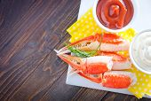 stock photo of cooked blue crab  - crab claws and sauce on a table - JPG