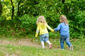 image of girlie  - two friends girls walking hand in hand - JPG