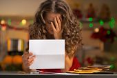 picture of sad christmas  - Closeup on frustrated young housewife with letter in christmas decorated kitchen - JPG