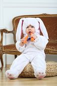 foto of bunny costume  - Little boy in costume bunny sitting on pouf with carrot  - JPG