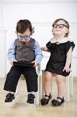 picture of lurex  - Little boy with tablet computer sitting on white chair next to happy girl with glasses - JPG