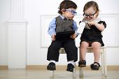 stock photo of little kids  - Two little kids in glasses sitting on white chairs - JPG