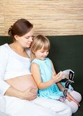 stock photo of fetus  - Little girl  with her pregnant mother looking at ultrasound scan of a fetus - JPG