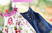 picture of habilis  - Fashion baby dresses hanging on a hanger on a green summer background - JPG