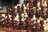 stock photo of chess piece  - Black and white chess pieces on a chessboard, closeup. Set of chess figures on the playing board
