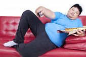 pic of obese man  - Overweight man eats pizza while watching tv at home - JPG