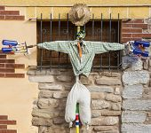 stock photo of scarecrow  - a scarecrow with a hat hanging on a wall - JPG