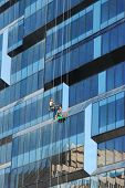 stock photo of window washing  - Two workers washing windows on side of new business building after construction - JPG