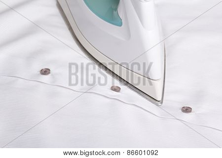 Close Up Of Iron Ironing Cotton Shirt