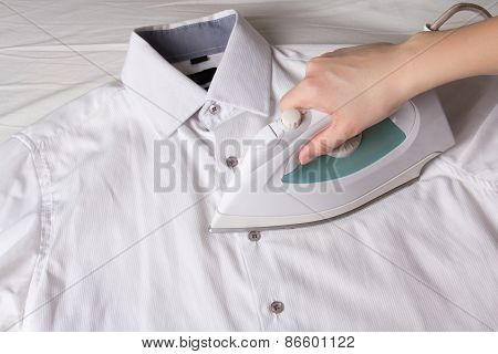 Iron In Female Hand Ironing Cotton Shirt