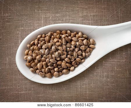 Hemp Seeds In A Wooden Spoon / High-res Photo Of Grain In White Porcelain Spoon On Burlap Sackcloth