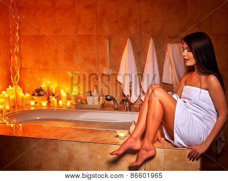 Woman relaxing at home luxury bath. Burning candle.