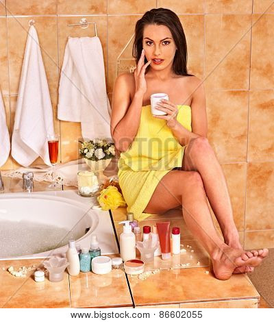 Woman applying moisturizer at bathroom. Visible legs.