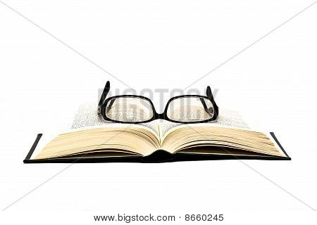 glasses on open book isolated on white with space for text