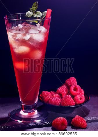 Red raspberry drink  with ice cube and plate with berry on black background. Cocktail card 19