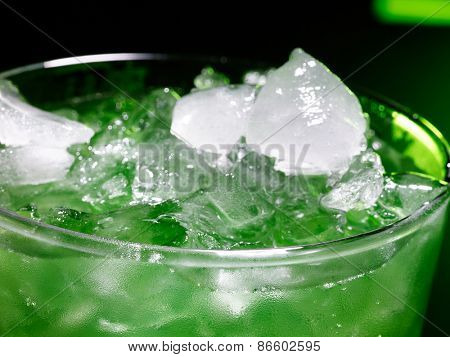 Green drink  with crushed ice on dark background. Top view.Close up.