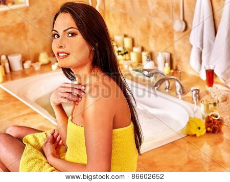 Woman relaxing at home luxury bath. Yellow towel.
