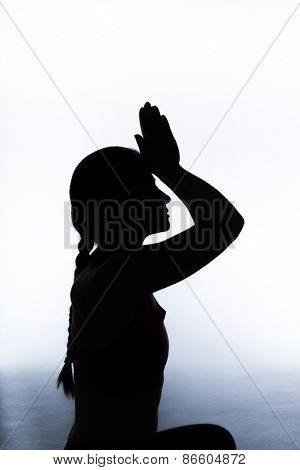 Silhouette of a woman practicing yoga in a studio.