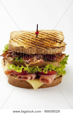 ham and bacon club sandwich on a white background
