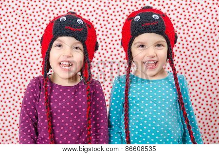 Twin Girls Are Smiling At The Camera And Being Happy. Little Children Are Joyful. Child Is Wearing A