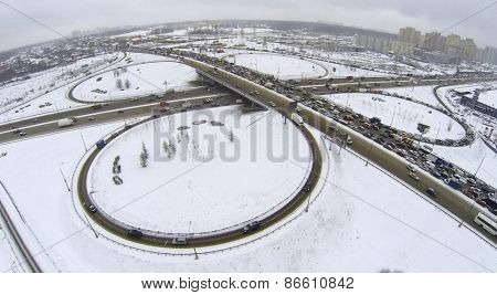 Highway overpass with transport traffic near city at winter day during snowfall. Aerial view