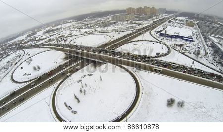 Cityscape with traffic on interchange of belt way at winter day during snowfall. Aerial view
