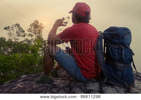 Hiker with backpack relaxing on top of the mountain drinking water and enjoying sunrise
