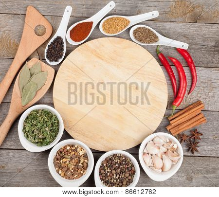 Herbs and spices on wood table background with blank cutting board for copyspace