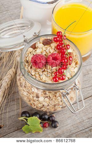 Healty breakfast with muesli, berries and orange juice. On wooden table
