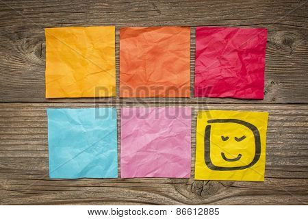 colorful blank sticky notes with smiley against grained wood