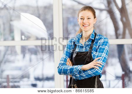 Young woman hairdresser in apron standing near window