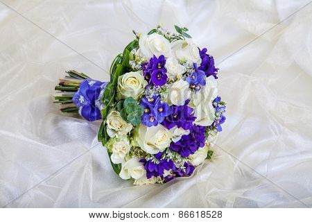 Wedding Bouquet Of The Bride Against A White Fabric